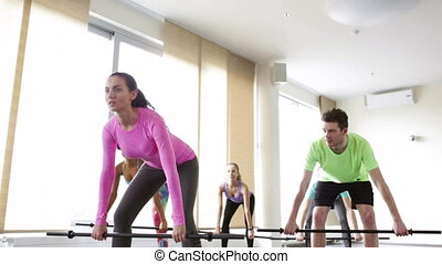 group of people exercising with bars in gym