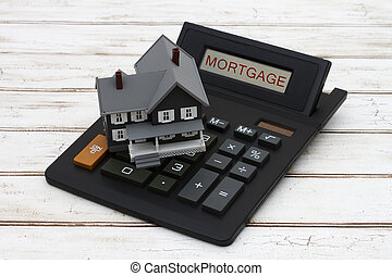 Calculating your mortgage payments, A gray model house on a...