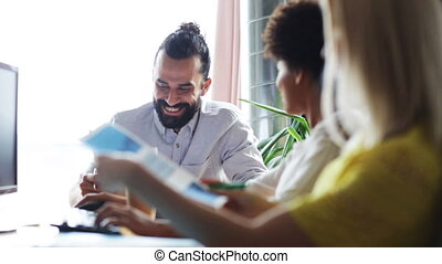 happy creative team with papers talking in office -...