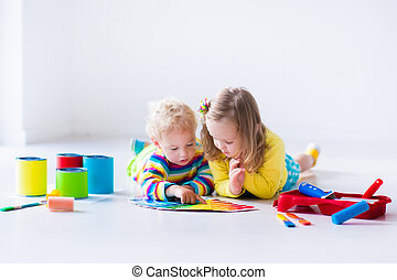 Children painting walls at home remodel - Family remodeling...