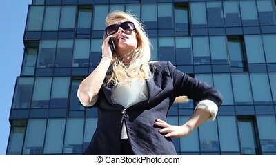 Business woman gives orders on her cell phone on the...
