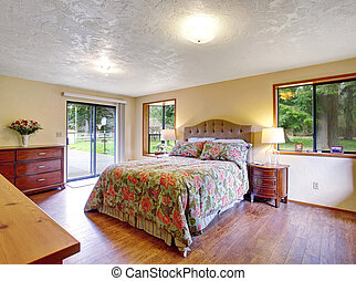 Gorgeous master bedroom with sliding lgass door and hardwood floor.