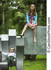 Little boy with his older sister on the Playground in the...