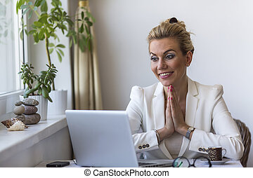 woman sitting with hands clasped - Young business woman...