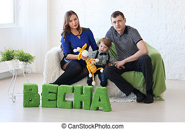 Family of three sit on white couch in room with green text on floor: Spring