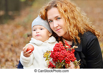 Woman with little daughter and rowanberry in autumn park at sunny day. Focus on mother