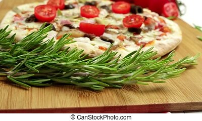 Pizza with bacon, olives and tomato on wooden table