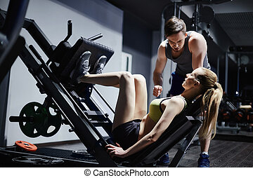 Exercising in gym - Attractive girl strengthening leg...