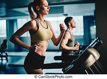 Woman on treadmill - Active young woman running on treadmill...