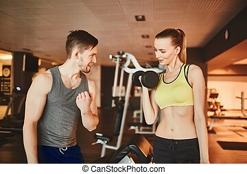 Doing exercise properly - Confident trainer consulting girl...