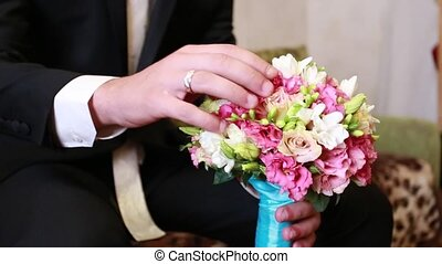 groom holding a wedding bouquet