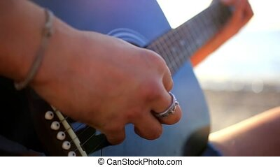 Musician hand playing guitar in the beach during sunset