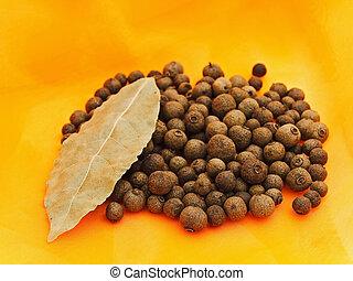 allspice and bay leaf over orange textile background