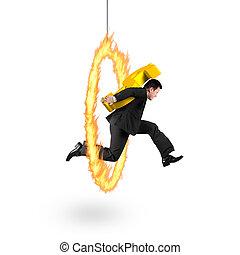 Businessman carrying golden dollar sign jumping through fire...