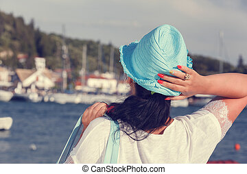 Woman with a hat looking at the sea - Back view of a woman...
