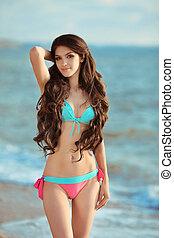 Fashion summer portrait of sexy beautiful girl with long healthy hair in bikini posing beside a sea, on beach.