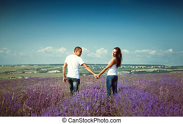 young attractive couple in a field in summer
