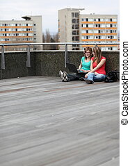 two female college students studying/working on a laptop computer on campus on a terrace