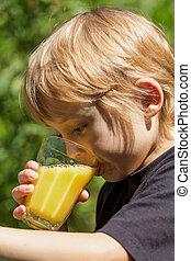 Little blond boy is drinking juice - Little blond boy is...