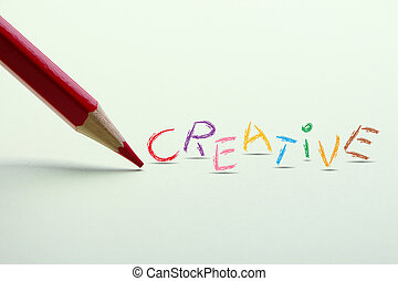 Creative word is standing on the paper with red pencil...