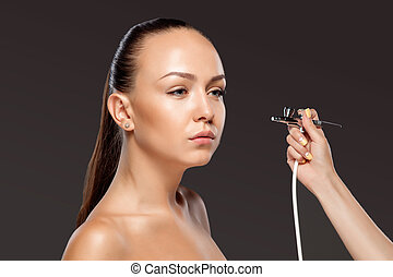 visagist making makeup for model with aerograph or airbrush...