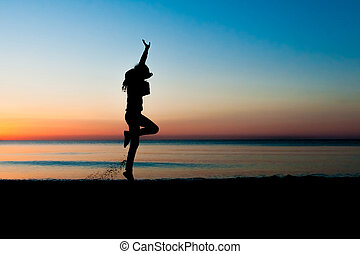 Silhouette of woman jumping in the air on the beach at...