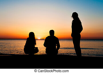 Silhouette of three friends in the morning at the beach...