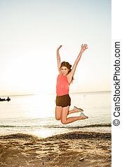 Happy young woman jumping o