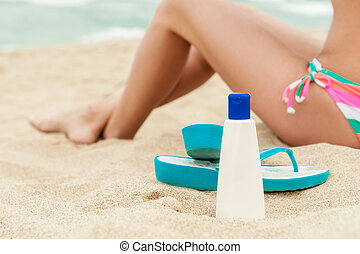 Woman applying sun protection lotion Bottle of sun...