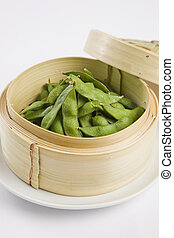 Edamame soybeans served warm with salt in bamboo steamer...