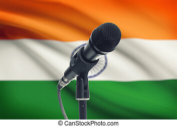 Microphone on stand with national flag on background - India...