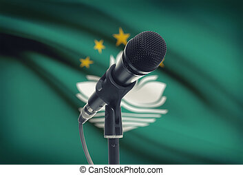 Microphone on stand with national flag on background - Macau...