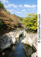 River flowing between a rock - Autumn river flowing between...