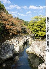River flowing between a rock - Autumn river flowing between...