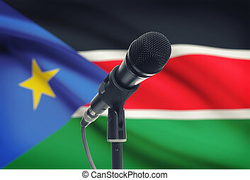 Microphone on stand with national flag on background - South...