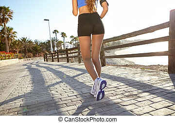 Young woman jogging outside in summertime - Low section of a...