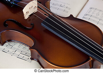 Violin resting on open sheet music book