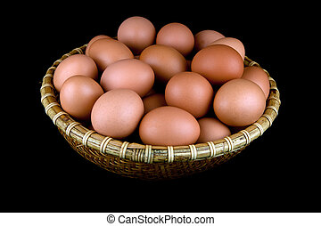 Basket of fresh hens eggs on black background - A whicker...