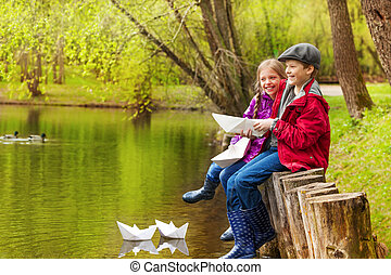 Laughing girl and boy near pond with paper boats - Laughing...