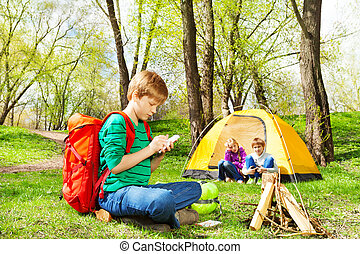 Boy with red backpack writes notebook at camping - Boy with...