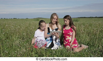 Woman and daughter using tablet computer in field