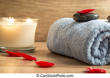 Luxurious spa setting with a rolled blue towel, romantic candle and black massage stone