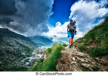 Lonely woman hiker in a mountain path