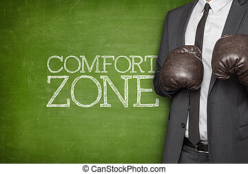Comfort zone on blackboard with businessman wearing boxing...