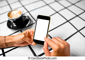 Using phone with coffee on background - Female hand using a...