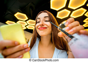 Woman with phone and drink in modern interior - Young woman...