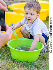 Cute baby boy is playing with water and posing in front of...
