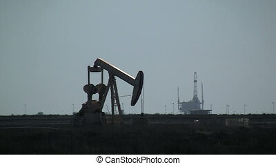 Pumpjack With Oil Rig In Background - Pumpjack with Oil Rig...