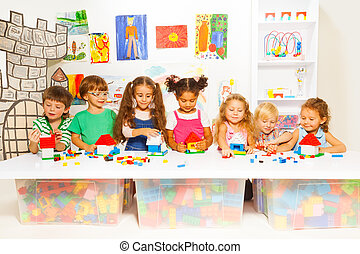 Little boys and girls constructing toy houses - Group of...