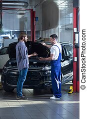 Customer talking with automobile mechanic - Photo of...